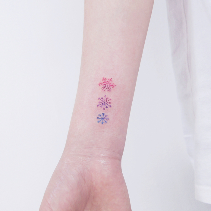 Tiny Colored Snowflakes on Wrist by tattooist_dal